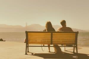 Couple assis sur un banc devant la mer