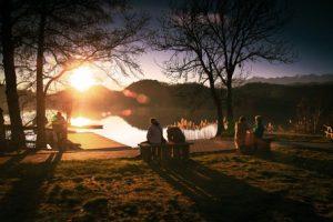Deux personnes dur un banc devant un coucher de soleil