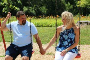 Couple heureux se tenant par la main sur une balançoire