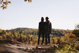 Couple debout face à une colline