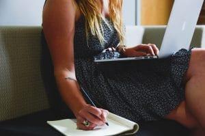 Jeune femme écrivant et travaillant sur un canapé