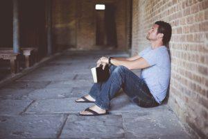 Homme mélancolique assis par terre