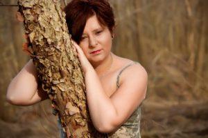 Femme pensive et mélancolique appuyée contre un tronc