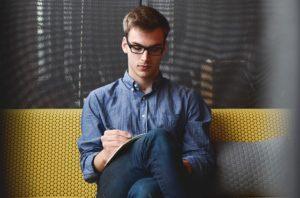 Jeune homme sérieux assis en écrivant