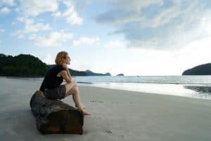 Femme seule assise sur la plage
