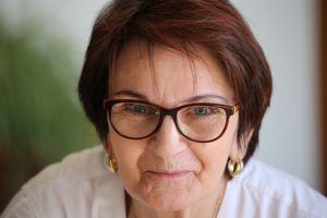 Femme dans la cinquantaine souriante et portant des lunettes