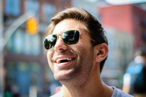 jeune homme souriant qui porte des lunettes de soleil