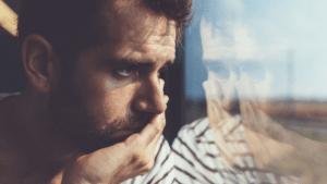 Homme anxieux qui regarde à travers une vitre
