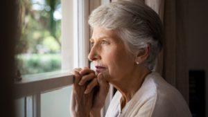 Femme soixantaine qui regarde par la fenêtre